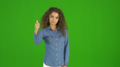 The curly businesswoman thumb down and stand on the green background. Real time Stock Footage