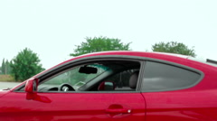Lady sits in a red sports car Stock Footage