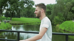 A young attractive guy with a beard is walking over a small bridge across river. Stock Footage