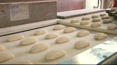 Bread rolls falling off the conveyor belt, dough production Stock Footage