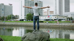 Attractive young man standing on a big stone by the river. Stock Footage