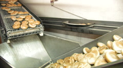 Bread rolls move from one conveyor belt to another Stock Footage