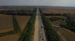 Road build construction widen multilane highway wind turbines transport traffic Stock Footage