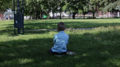 The little sad boy in the blue shirt was lost in park and sitting on grass alone Stock Footage