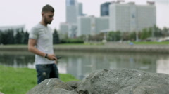 The guy in casual clothes on a bank of the river is calling on cell phone. Stock Footage