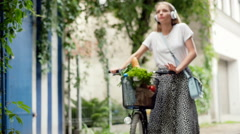 Pretty girl walking with bicycle and enjoying listening music, steadycam shot Stock Footage