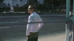Back view. Man in glasses at the bus stop. Stock Footage