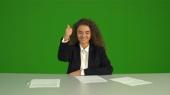 The curly businesswoman thumb up and sit on the green background. Real time Stock Footage