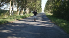 Adult man running outdoors in a forest path. Old man jogging outdoors Stock Footage
