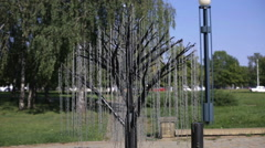 Metal tree in the park. Branches made of chains are swinging on the wind. Stock Footage