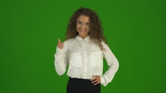 The curly businesswoman thumb up and stand on the green background. Real time Stock Footage
