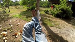 Man's bare feet shown lying on hammock Stock Footage