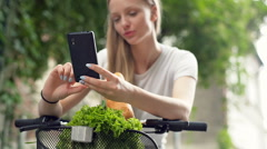 Pretty girl leaning on handlebars and doing selfies on smartphone Stock Footage