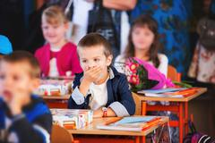 Young first grade student sitting at desk on his first day at school Stock Photos