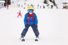 Young child, skiing on snow slope in ski resort in Austria Stock Photos