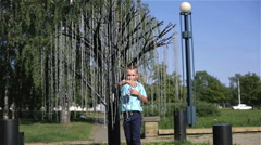 A little boy in a blue shirt and trousers examines branches of the chain. Stock Footage
