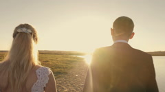 Bride and groom running through the field to meet the sun at sunset Arkistovideo