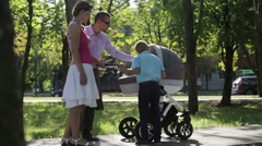 Sunny day. Young family on a walk in the park. Fresh air and good mood. Stock Footage