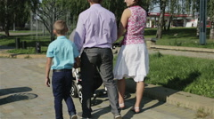 Family summer walking in a green park. Mother in white skirt and pink blouse Stock Footage