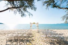Simple style wedding arch and decoration, venue, setup on tropical beach Stock Photos