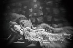 Antique carved wooden Buddha, reclining Buddha posture. selective focus. Stock Photos
