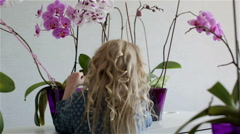 View from back. Little girl with white curly hair is taking care for the flowers Stock Footage