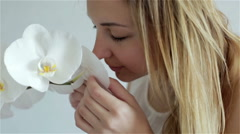 Beautiful young woman smelling white orchids and touching the petals. Stock Footage