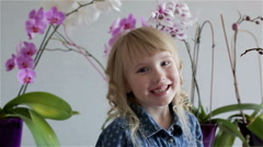 Close up. Smiling child girl face near purple and white orchids. Stock Footage