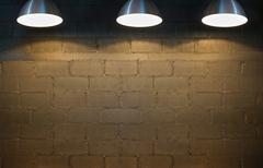 Old interior room with brick wall and three spotlights. Stock Photos