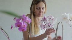 Young beautiful woman in white dress is taking care of delicate colorful orchid. Stock Footage