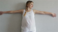 Young pregnant woman standing at the gray wall and blissfully waving her arms. Stock Footage