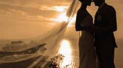 Silhouette couple kissing over sunset background. Stock Photos
