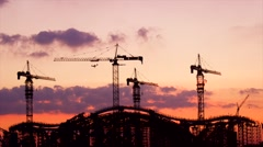The rising sun appears from behind a silhouette building of the construction Stock Footage