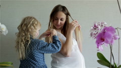 Little blonde daughter is plaiting pigtail from her mother's hair. Stock Footage