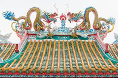 Chinese dragon and pheasant on the roof of the shrine. Isolated. Stock Photos