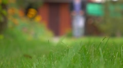 Green grass and man with lawn mower approaching the camera. 4K bokeh background Stock Footage