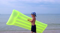 A child on the beach, a boy carries Inflatable Beach Mattress For Swimming Stock Footage