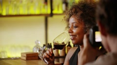 Beautiful black woman on photo session in bar. She drink wine and laughs Stock Footage