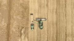 Aerial view of combine harvester loading wheat into a trailer Stock Footage