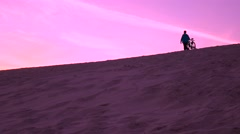 Man with his bike walking over sand dune, purple sunset colors. 4K video Stock Footage