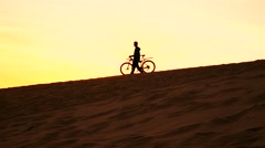 Silhouette of a man with his bike walking on sand dune, yellow sunset colors. 4K Stock Footage