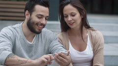 Young Smiling Woman And Man are Using Mobile Phone Outdoors. Stock Footage