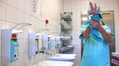 Female doctor performs a surgical hand and arm scrub Stock Footage