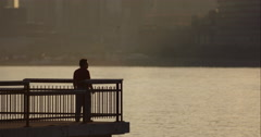 Man stands on end of pier as NYC Waterway boat passes by in slow motion Stock Footage