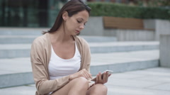Young Attractive Woman is Sitting on the Stairs and using Mobile Phone Outdoors Stock Footage