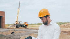 Male bearded construction boss dressed in a hard hat controls construction Stock Footage