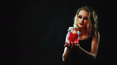 St. Valentine's Day. A girl holding a glass jar with a red heart inside. Stock Footage