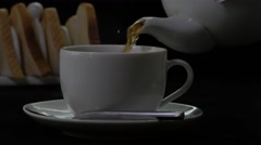 Tea being poured from a white teapot into a cup, toast in rack in background Stock Footage