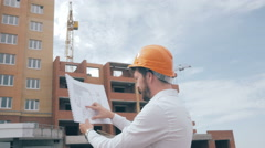 Architect looking at blueprints at a building site Stock Footage