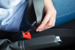 Close Up Of Person In Car Fastening Seat Belt Stock Photos